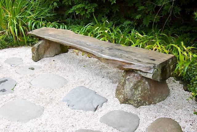 Оригинальная скамейка построенная из бревна и камней