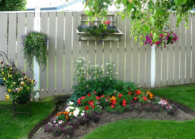 Забор можно увешать всевозможными контейнерами для растений и цветов