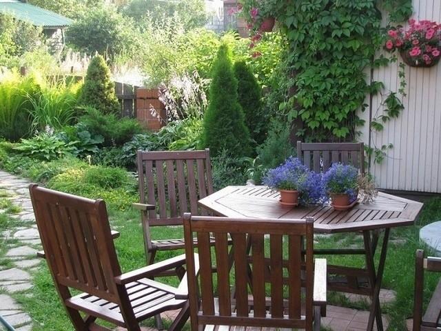 уголок в саду из декоративной стенки, столика и скамейки